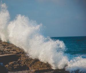 Photo of ocean waves breaking against a rock