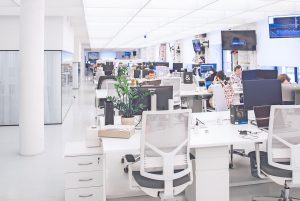 Open plan office with rows of desks and computers, at some of which people are working
